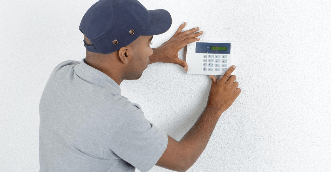 An HVAC specialist replaces an old wall heater with a modern thermostat.