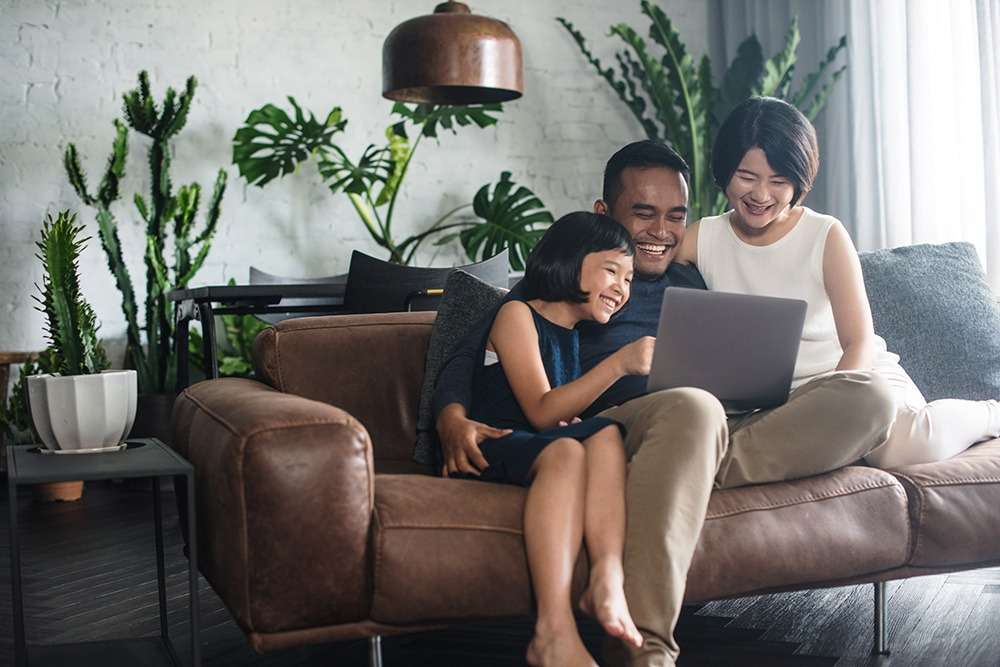 Happy Asian family using the computer together at home.