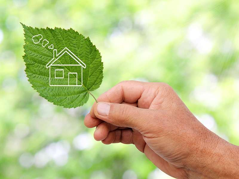 Eco house concept, hand holding eco house icon in nature